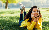 Image of happy young teenage girl smiling and relaxing outside in nature green park. Cheerful young beautiful woman lying outdoors on green grass in city park.
