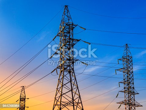 High voltage electricity pylons and transmission power lines on the blue sky background.