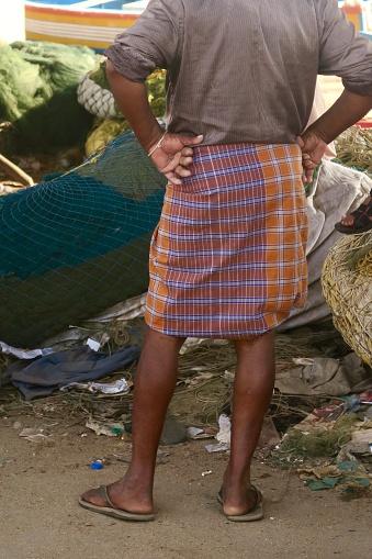 Hindu Indian fisherman wearing traditional lungi skirt to cope with hot summer heat on Kollam Beach, Kerala, South India.
