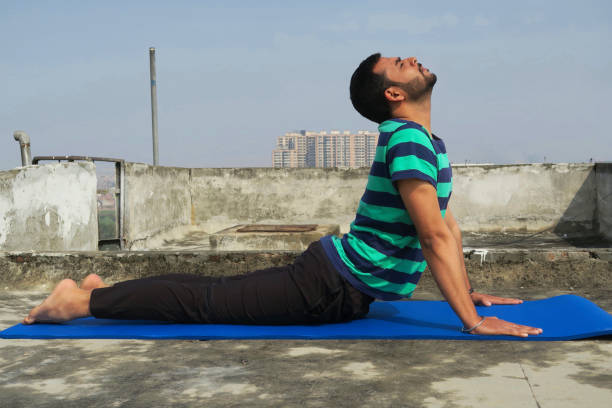 Image of Hindu Indian man practicing upward facing dog (Urdhva Mukha Svanasana) yoga position on rooftop photo, Delhi, India Indian, Hindu male performing the upward facing dog (Urdhva Mukha Svanasana) yoga position as part of the Surya Namaskar (salute to the sun) sequence on a blue fitness mat. upward facing dog position stock pictures, royalty-free photos & images