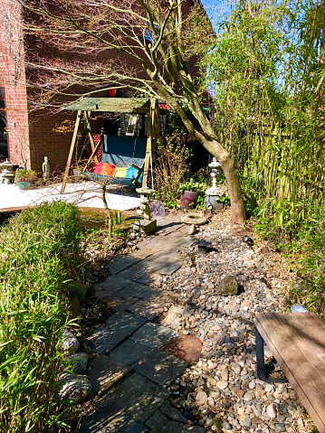 Image of home exterior, garden decking patio by house with green swing seat beside koi pond surrounded by bamboo hedge, tiled slate footpath