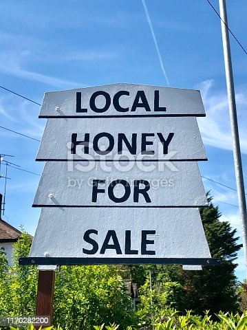 Stock photo showing a 'local honey for sale' sign in a garden so people can stop and buy.