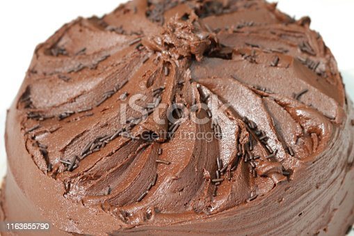 Stock photo of homemade black forest gateau with dark cherries and jam / hot chocolate fudge cake recipe iced with rich ganache icing made with cream and cocoa, home baked chocolate sponge cake with sprinkles, for after dinner pudding / eating dessert food