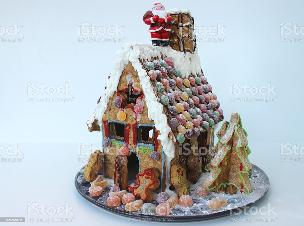 Image of homemade Christmas gingerbread house decorated with sweets / biscuits stock photo