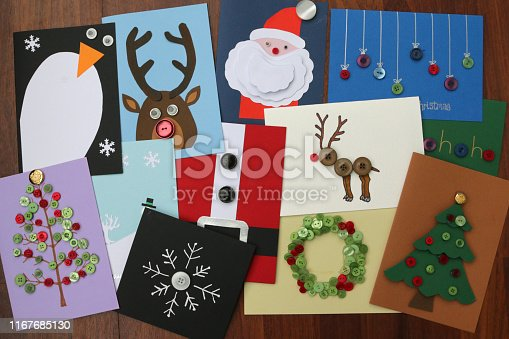 Stock photo of homemade DIY easy Christmas cards designs with cut-outs Santa Claus, snowmen, snowflakes, reindeer, Xmas trees with baubles, wreaths, penguins, buttons and how to make Father Christmas card ideas for happy holidays, handmade Xmas greetings cards