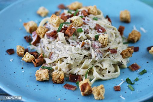 Stock photo showing an elevated view of  turquoise blue plate with a portion of homemade fettuccine carbonara, using a traditional Italian recipe. The pasta is mixed with eggs, herbs, crispy bacon lardons and pancetta, prosciutto slices, grated Italian Parmesan cheese and garlic.