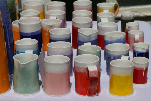 Image of homemade / handmade pottery mugs and jugs in rainbow colours, thrown on potter's wheel earthenware clay, glazed and fired in kiln, displayed as mug group for cup of coffee / tea with cups in shades of red, pink, yellow, green, orange, blue glazes