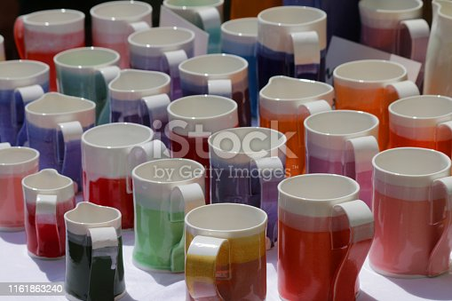 Stock photo of homemade / handmade pottery mugs and jugs in rainbow colours displayed as mug group for cup of coffee / tea with cups in shades of red, pink, yellow, green, orange, blue glazes, glazed and fired in kiln