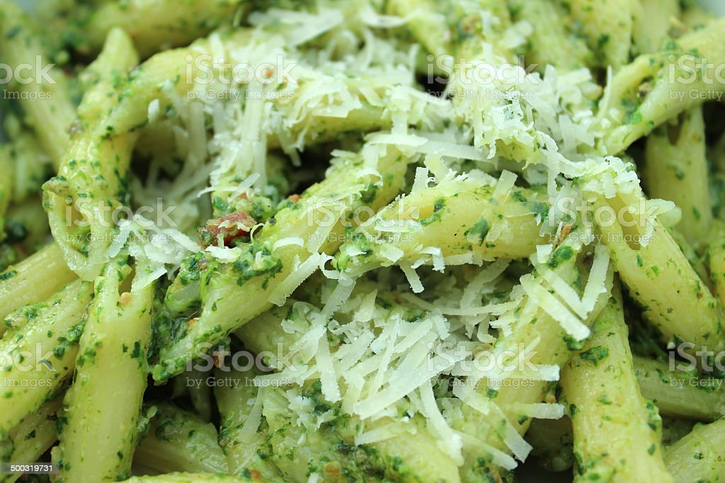 Image of homemade pesto pasta topped with grated parmesan cheese royalty-free stock photo