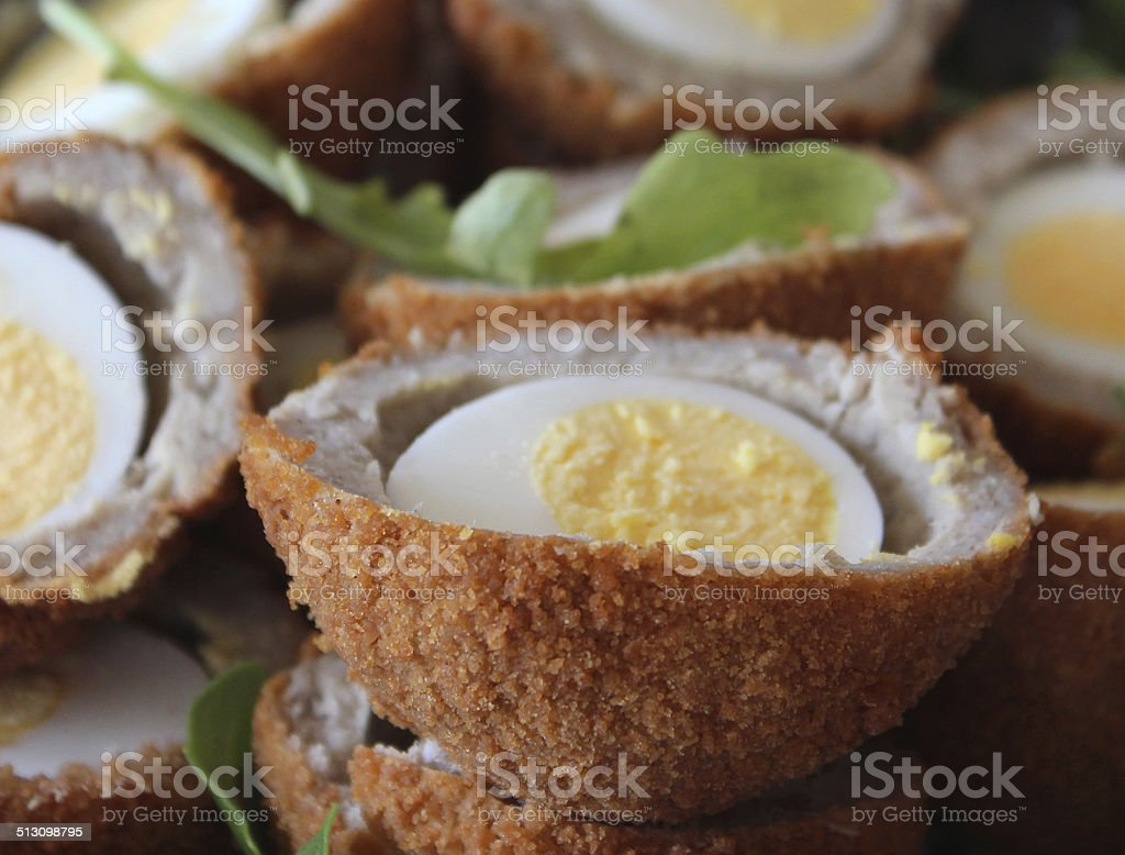 Image of homemade Scotch eggs sliced in half, party food stock photo