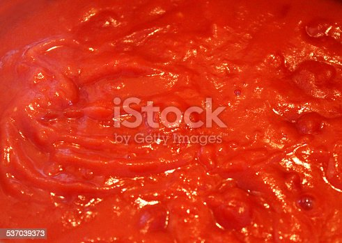 Photo showing some homemade tomato sauce / ragu sauce cooking in a saucepan, pictured simmering away and reducing on a low heat.  This is a rich pasta sauce made with tomatoes, tomato puree, finely chopped onion and lots of freshly picked herbs.