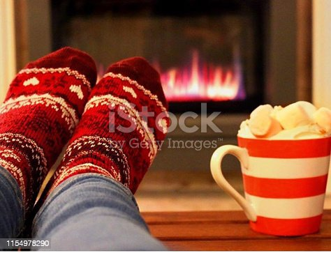 Stock photo of frothy hot chocolate drink in mug with gas fire in background and feet on the coffee table at Christmas . This man is wearing socks to warm up in winter weather. The hot chocolate is topped with delicious pink and white marshmallow sweets