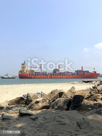 Stock photo of huge cargo ship entering the Kochin port for cargo loading / unloading down the sea channel, ship is being moored by a tug boat to get into port side Kochi port, Kerala, India