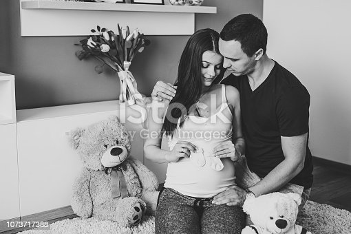 istock Image of husband holding belly of pregnant wife, socks for baby in hands. Pregnant woman or girl and man hugging tummy at home. Loving Couple. Parenthood concept. Baby Shower. Black and white photo. 1073717388