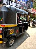 Kovalam, Kerala, India - March 31, 2019: Black and yellow auto rickshaws waiting for passenger fares outside a restaurant in a Kovalam street, Kerala, India.