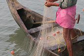 Stock photo of Indian fisherman wearing traditional pink lungi sarong / dhuti catching fish in small wooden fishing boat. This fisherman is pulling in white nylon fishing net by hand catching the small fish for seafood market, Kollam, Kerala, South India
