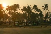 Kollam Beach, Kerala, India - March 29, 2019: Stock photo of sunrise at Kollam Beach, Kerala, India with local Indian fishermen untangling fishing nets after landing an early morning catch of the day.