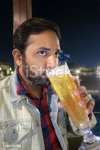 Stock photo of Asian Hindu man drinking beer alcohol with fizzy bubbles, tipsy after social event dinner party, drinking too much. Sitting at table wearing denim jacket and red check shirt at night with garden lighting, tipsy holding tall pint glass