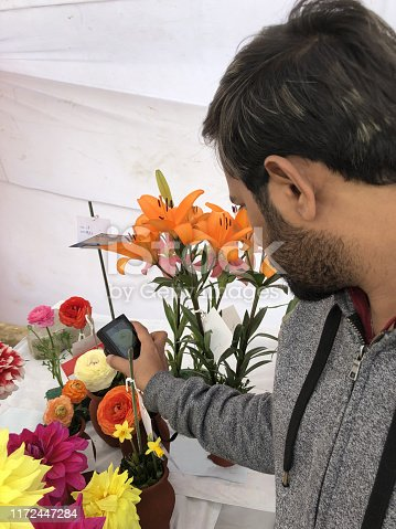 Stock photo of Indian hindu man wearing grey hoodie is taking photos of tiger lilies, ranunculus, chrysanthemums flowers in flower pot, summer bedding plants with small size / compact pocket camera at annual garden festival / flower festival in Delhi, India