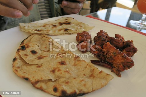 Stock photo of Indian men eating at Indian restaurant meal with food served in plate, spicy deep-fried chicken pakoras recipe, garlic naan, raita, meat dish served with Indian salad of spiralised cucumber and carrot, Delhi, India