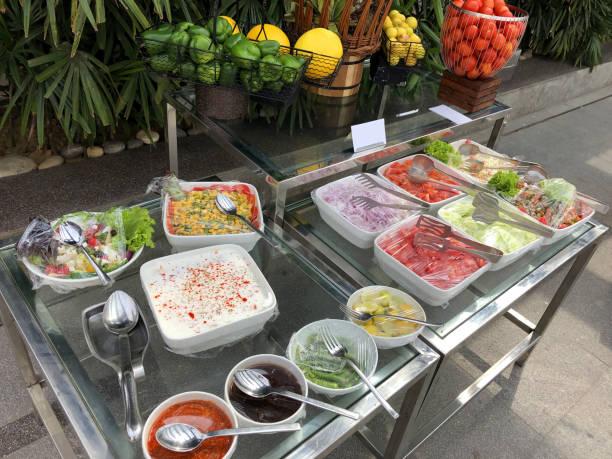 Bild von indischen Party-Food-Buffet im Freien im Garten mit weißen Gerichten / Terrinen von Salat-Lebensmittel bedeckt in Küche Kunststoff Klebefolie Folie Lebensmittel wickeln auf Metall-und Glastische, ZuckermaisSalat, Raita, rote Zwiebel, Salatblätt – Foto