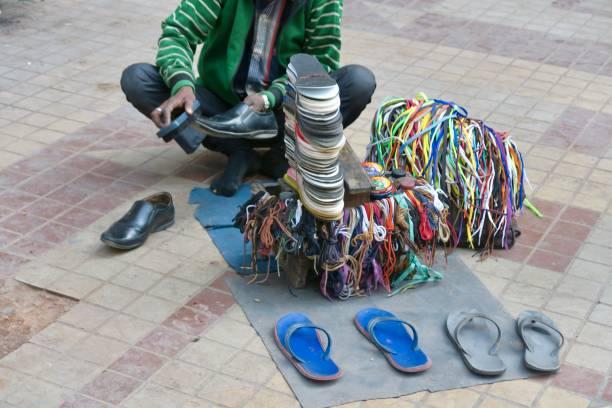 bild von indischen schuhmacherinnen, polieren und reparatur von schuhen foto über delhi zahlung, obdachlose schuh-glanz junge/schuster in indien billige handarbeit arbeit - flip flops reparieren stock-fotos und bilder