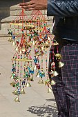 Image of Indian street market trader selling colourful rainbow nursery mobile with beads, toy elephants and bells, children's mobiles for baby nursery bedrooms