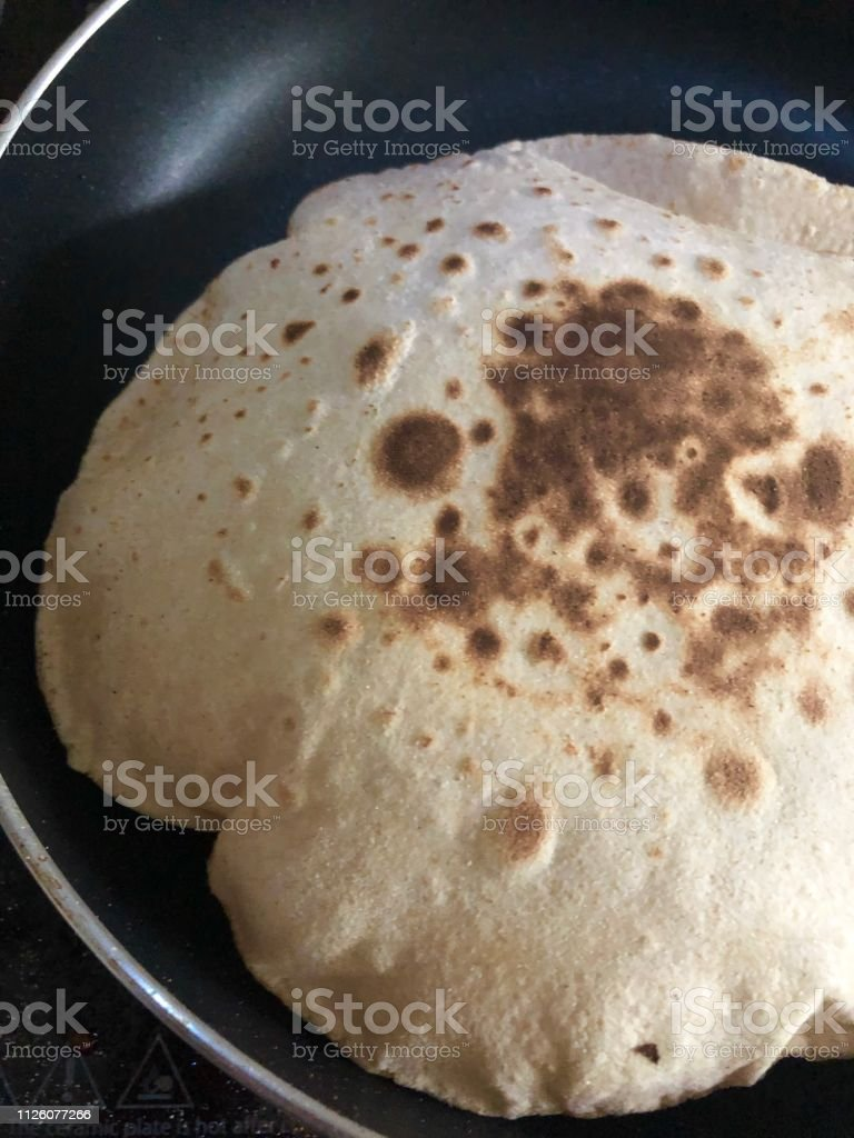 Image of inflated roti / chapatti cooking in kitchen non-stick frying pan photo, wholewheat atta flour stock photo
