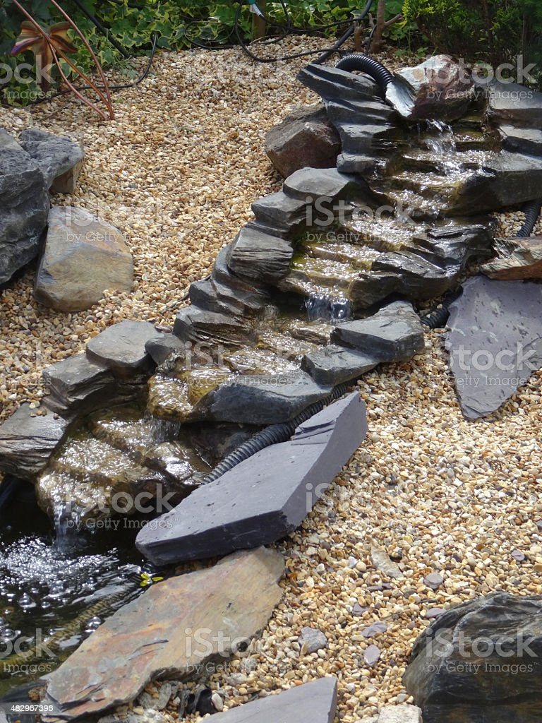 Image of interconnecting plastic / fibreglass pond waterfalls on gravel slope stock photo
