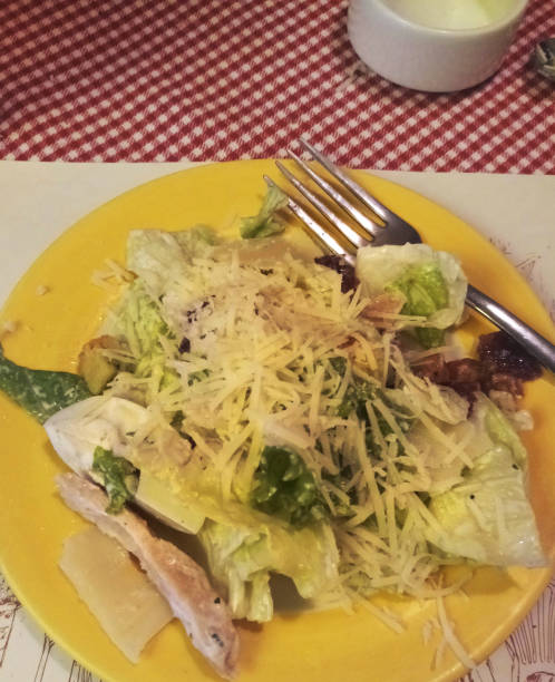 image of italian restaurant food starter for romantic meal for two, with chicken caesar salad, non veg salad photo, grated parmesan cheese, iceberg lettuce, sliced chicken, salad dressing, yellow dinner plate, chicken caesar salad and appetiser croutons - appetiser stock photos and pictures