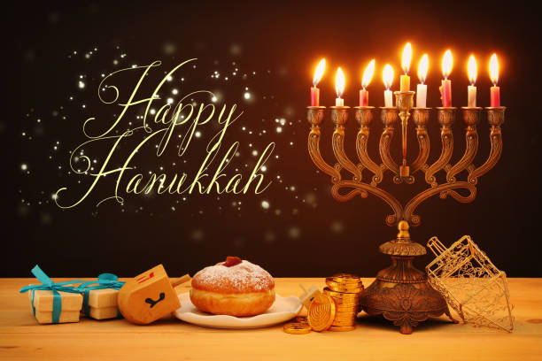 image of jewish holiday Hanukkah background with traditional spinnig top, menorah (traditional candelabra) and burning candles. stock photo
