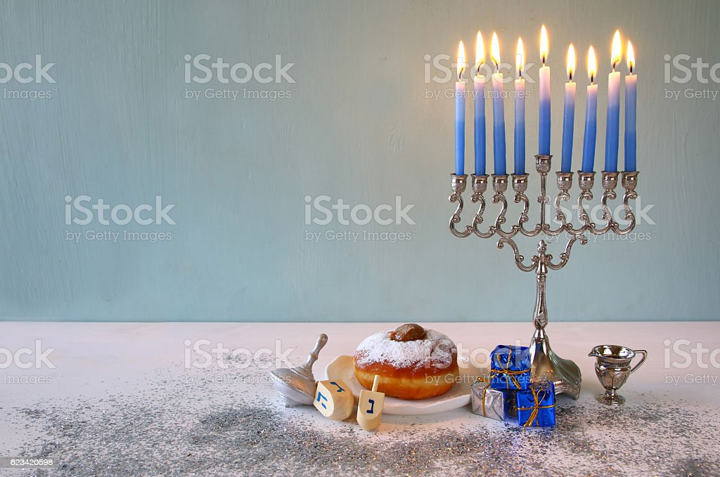Image of jewish holiday Hanukkah with menorah , donut and wooden...