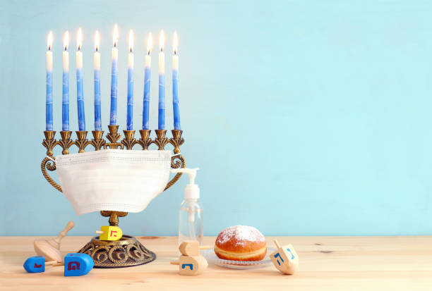Image of jewish holiday Hanukkah with menorah (traditional Candelabra), donut, wooden dreidel (spinning top). Coronavirus prevention concept, medical mask and and sanitizer gel stock photo