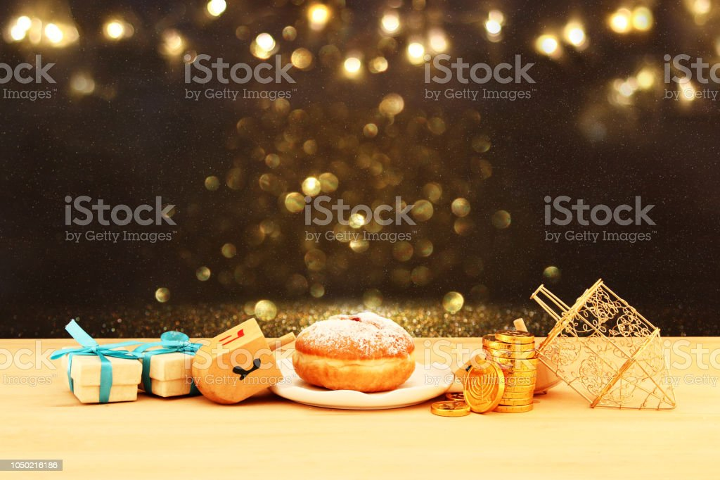 Image of jewish holiday Hanukkah with wooden dreidels and donut on...