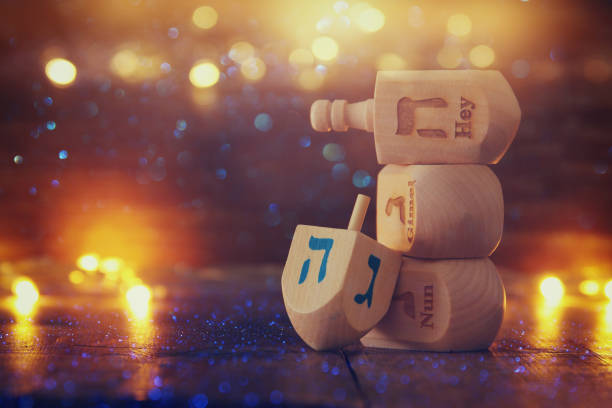 Image of jewish holiday Hanukkah with wooden dreidels colection (spinning top) and glowing gold lights stock photo