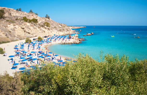 image of konnos beach near agia napa, cyprus. many blue sun loungers and umbrellas on white sand near transparent blue water in a bay and rocky hills. cloudless day in fall - cyprus стоковые фото и изображения