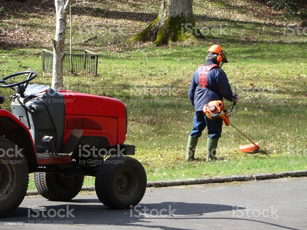 Image of landscape gardener working outside, strimming grass with lawn-strimmer stock photo