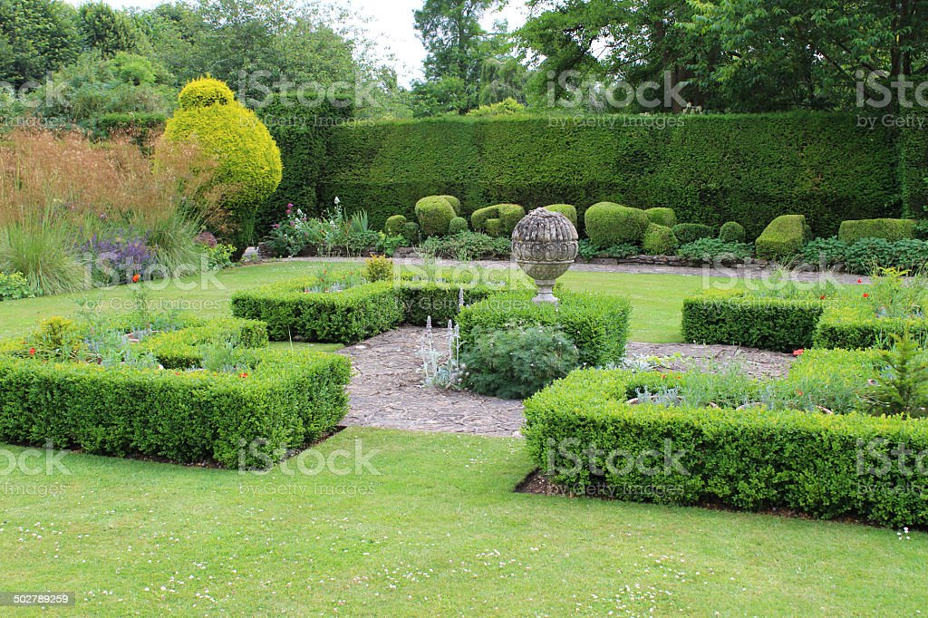 Photo showing a spreading lawn with a centerpiece knot garden, with...