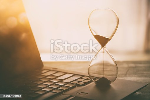 Image of laptop over wooden desk at office, workplace or home and hourglass. Vintage filtered
