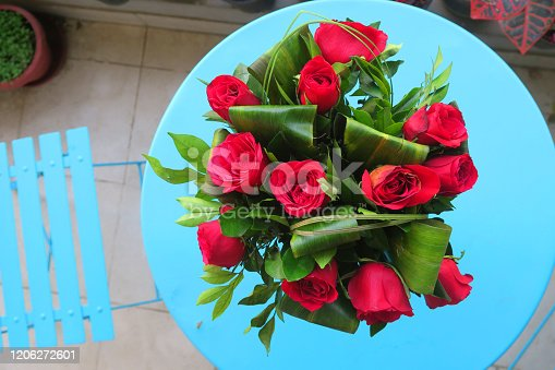 Stock photo showing large bunch of red roses flowers with close-up of petals, green leaves and blooms, red rose floral arrangement bouquet for Valentine's Day romantic gesture of love for couple, romance photo Romantic Valentine's Day, red roses isolated against a turquoise blue table with chair, alfresco
