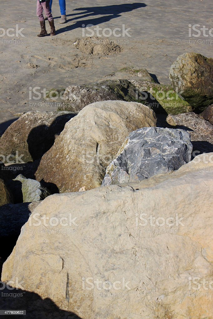 Image of large rocks / boulders forming sea defence on sandy-beach stock photo