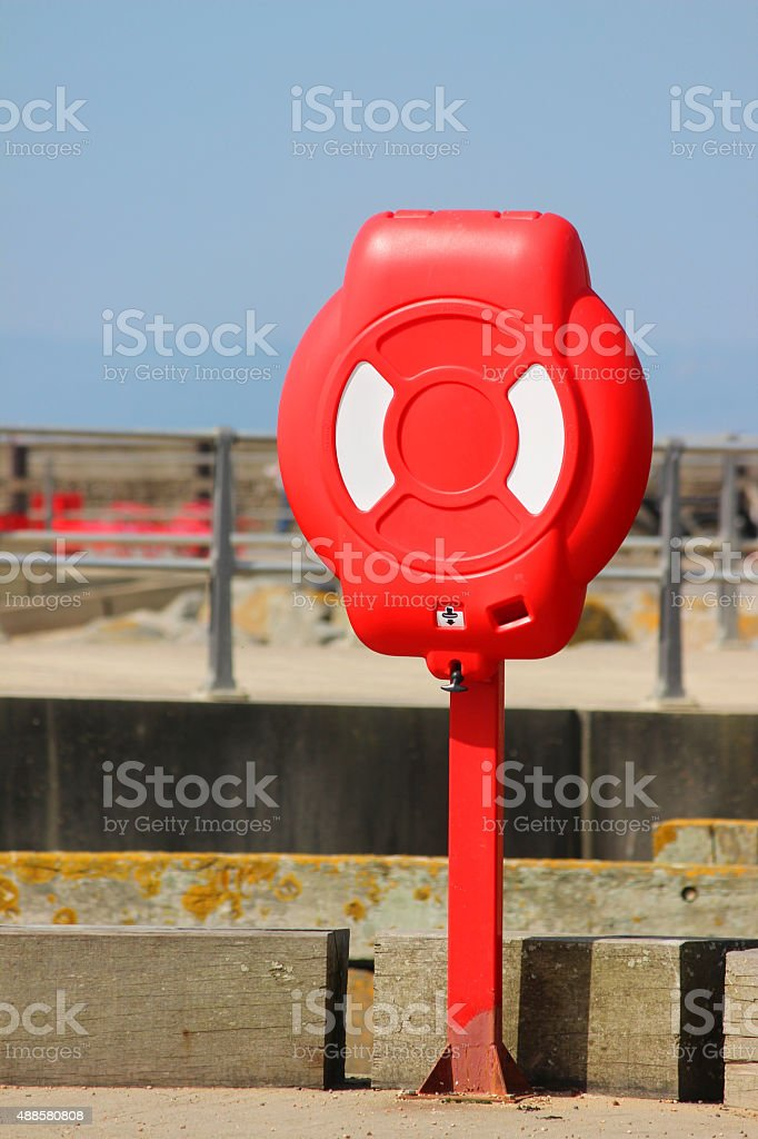 Image of lifering / lifebuoy at beach harbour, next to sea stock photo