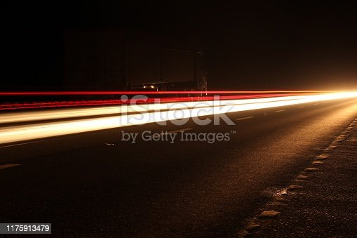 Stock photo showing the head and tail lights of cars travelling on a dual carriageway at night, movement captured with long exposure.