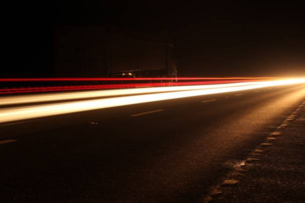 Image of lightstream effect photography technique, long exposure picture of the head and tail lights of cars travelling on a dual carriageway at night stock photo