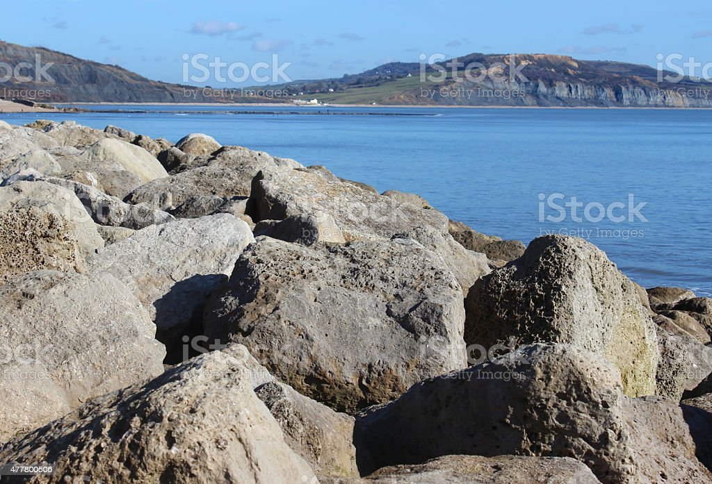 Image of limestone pile on beach, rock armour sea defence stock photo