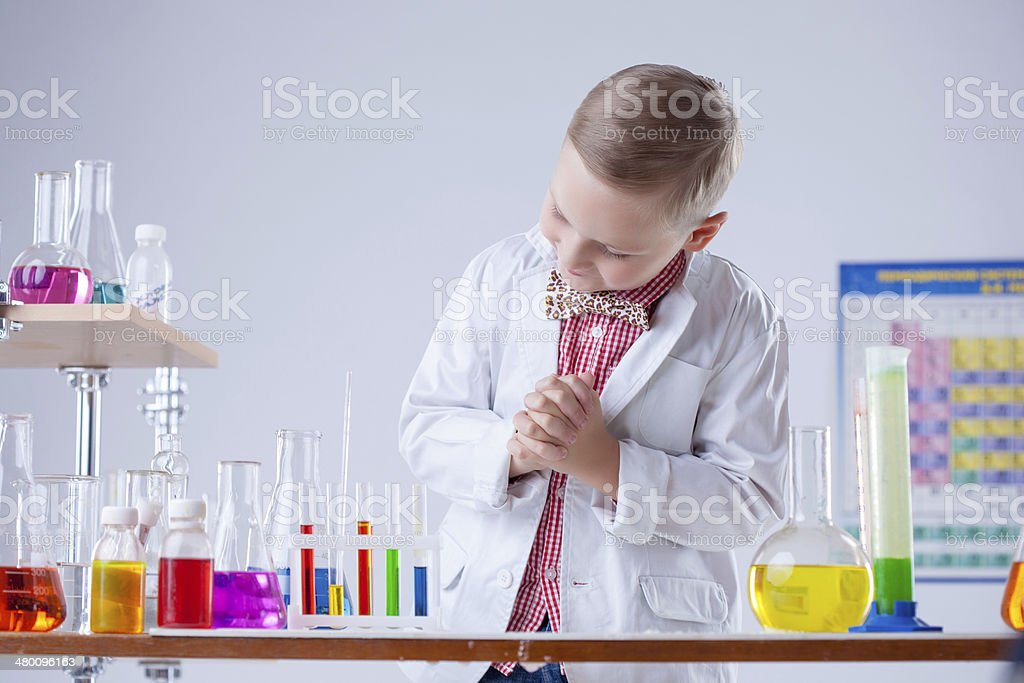 Image of little scientist posing with reagents stock photo