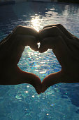 Image of love heart hands forming silhouette shape against sunset sparkling blue swimming pool water ocean effect, heart hand shape formed with fingers concept wallpaper photo for couple's love, romance and wedding theme with Valentine's Day heart symbol