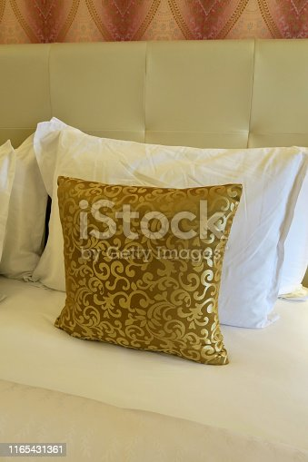 Stock photo showing a luxury double king size bed, which looks opulent with its clever use of colour, cream tall leather studded headboard against the wall and matching golden scatter cushions, home furnishings and bedroom interior design with fleur de lys pattern design
