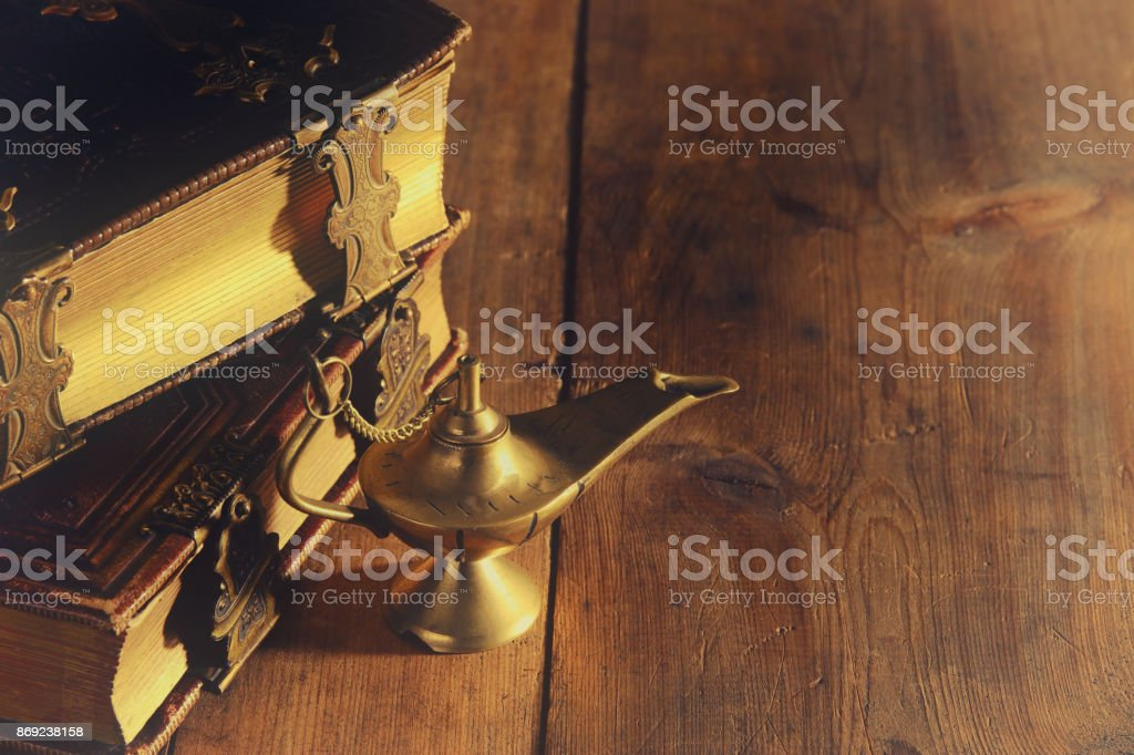Image of magical aladdin lamp and old books. Lamp of wishes. stock photo