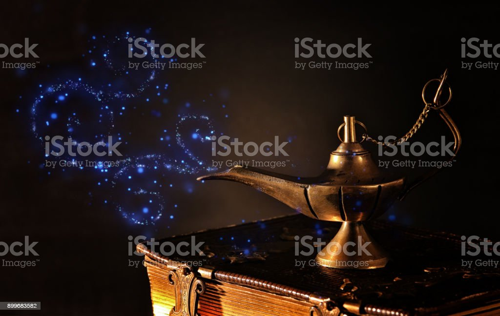 Image of magical aladdin lamp on old books. Lamp of wishes stock photo
